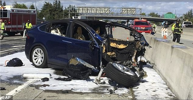 Tesla is under investigation after 127 complaints were sent to the National Highway Safety Administration (NHTSA) claiming certain models experienced 'sudden unintended acceleration'. Pictured is an incident in 2018 in Mountain View, California where a Tesla electric SUV crashed into a barrier after it suddenly accelerated