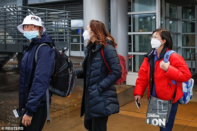 The second US case of coronavirus has been confirmed in a 60-year-old woman who traveled to Chicago, Illinois, from Wuhan, China - where the virus originated. Pictured: Passengers wearing masks arrive at O'Hare International Airport on Friday
