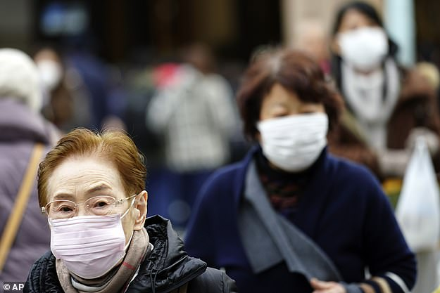 Japan confirmed its first case of infection from the new virus - a man in his 30s from Tokyo who had recently visited Wuhan. Pictured, pedestrians in Tokyo wearing protective masks