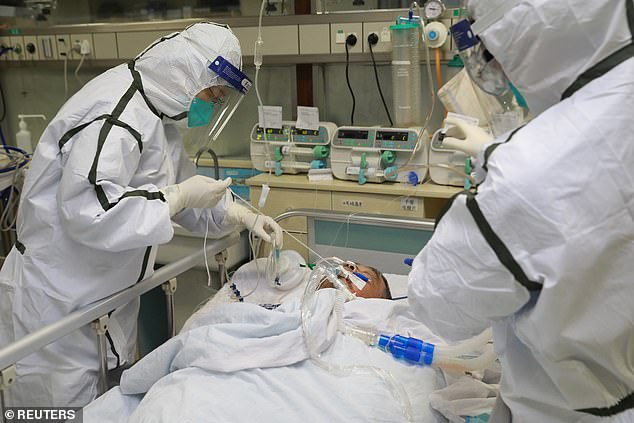 She returned to Chicago on January 13, but did not show symptoms until several days later. Pictured:Medical staff in protective suits treat a coronavirus patient at Zhongnan Hospital in Wuhan, January 27