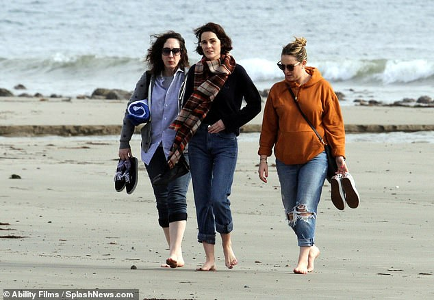 Barefoot stroll:The beauty wrapped up in a tan and red checked scarf and wore a cross-body bag as she walked barefoot across the beach