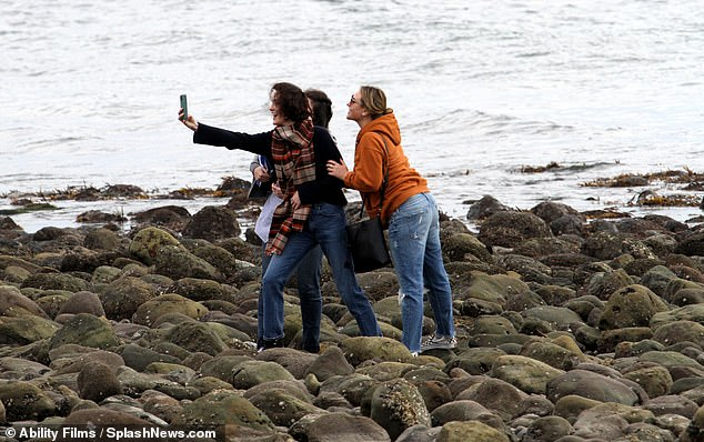 Photo time: Michelle looked delighted as she took a scenic photo with her pals on the rocks