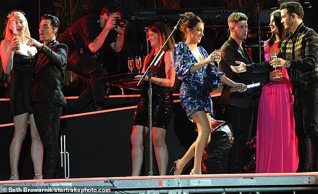 Family fun: Kevin Jonas' wife Danielle, pictured centre in a blue frock, also joined the group on stage