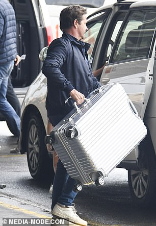 Heavy lifting: The TV presenter was later seen loading up the the family's suitcases into a taxi