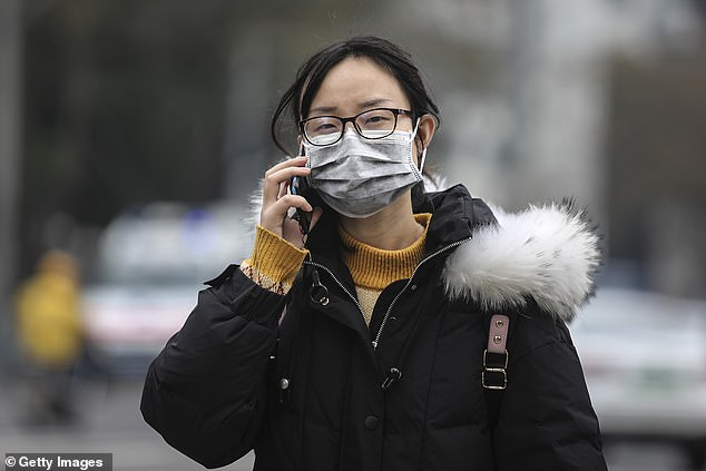 People carrying the novel coronavirus may only have mild symptoms and assume they have a common cold, British scientists warned. Pictured, a woman wearing a mask while walkingpast the closed Huanan Seafood Wholesale Market, which has been linked to cases of Coronavirus