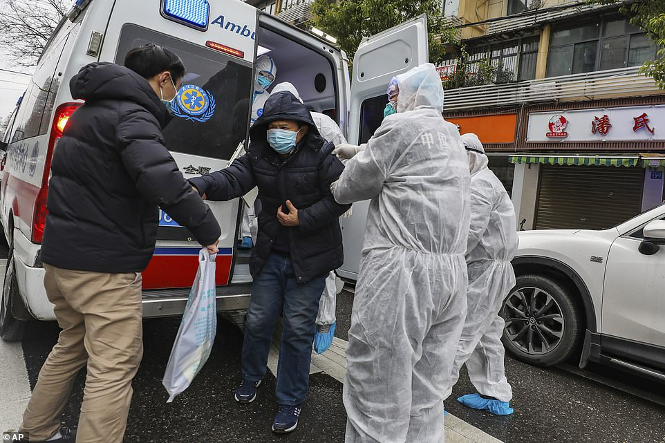 Medical workers in protective gear help a suspected coronavirus patient get out of an ambulance in Wuhan