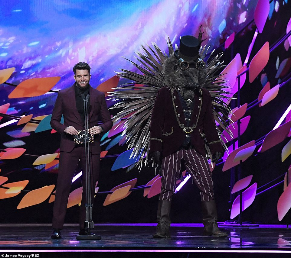 'It's nice to see Caroline Flack back on TV!' Joel Dommett took to the stage, joined by Hedgehog from his show The Masked Singer - an unknown person dressed up in an oversized animal costume