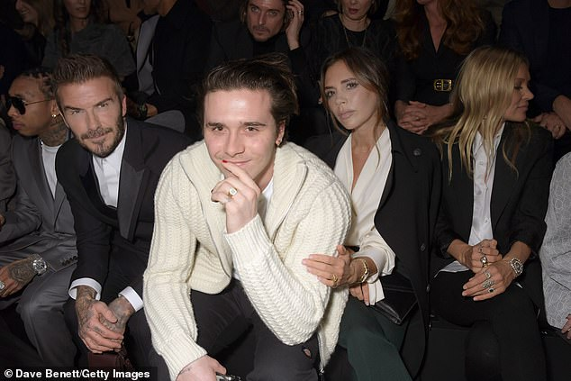 Strike a pose: Further lighting up the front row in Paris was the Beckham clan, consisting of matriarch Victoria, 45, husband David, 44, and their eldest son Brooklyn, 20