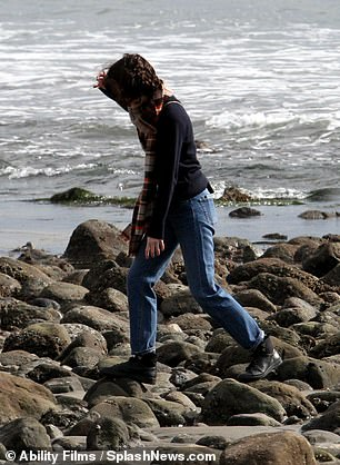 Casual cool: Michelle bundled up as she walked on the rocks