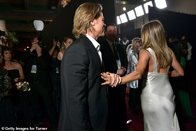 Touchy-feely: Brad briefly held Jennifer's hand as she turned away from him