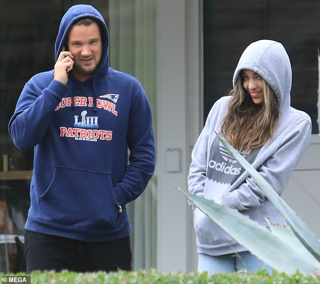 Casual Friday: The 39-year-old paired the Patriots Super Bowl hoodie with black gym shorts and matching Nike trainers