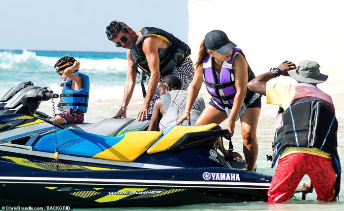 Raring to go: Simon helped steady the jet skis ahead of their fun time on then water