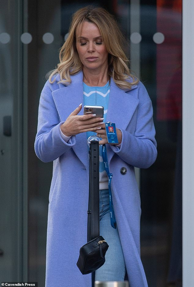 Shock:Amanda Holden was glued to her phone on Friday morning as she emerged in Manchester, shortly after former This Morning co-host Phillip Schofield came out as gay