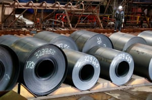 A ThyssenKrupp steel worker walks next to finished steel coils at the rolling mill department of the German steel maker in Duisburg, Germany.