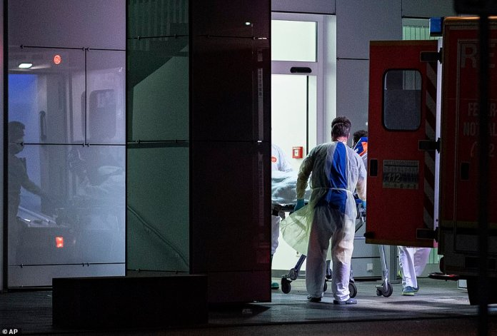 Medical staff in carry the first person infected with the coronavirus in the German state of North Rhine Westphalia out of an ambulance into the University Hospital in Dusseldorf