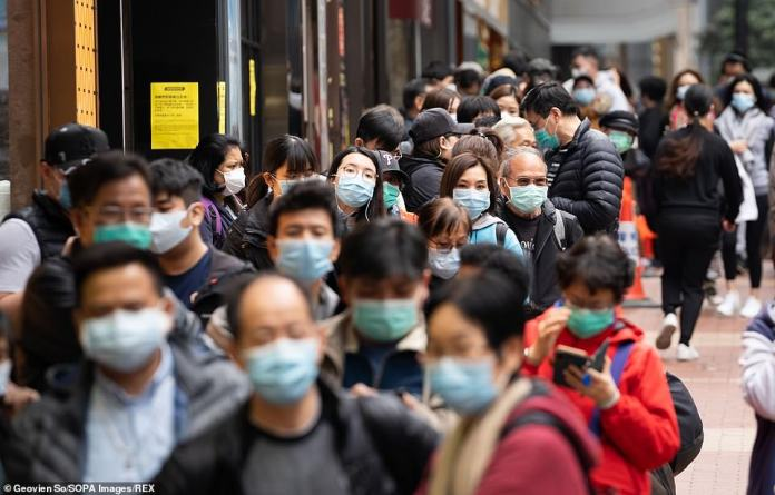 People in Hong Kong line up outside a pharmacy to buy surgical masks which are in shortage in the city