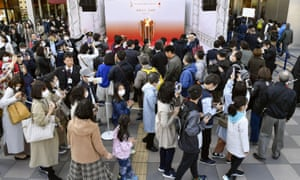 People gather to take a look at Olympic flame on display in Sendai, Miyagi prefecture, north of Tokyo Saturday, March 21, 2020.
