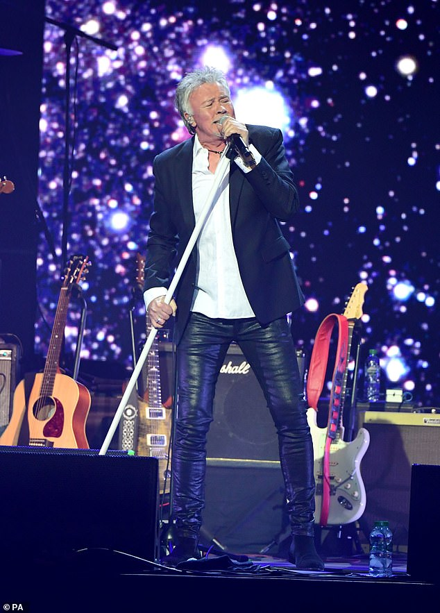 Paint it black! SingerPaul Young wore a black blazer over a white shirt and leather trousers