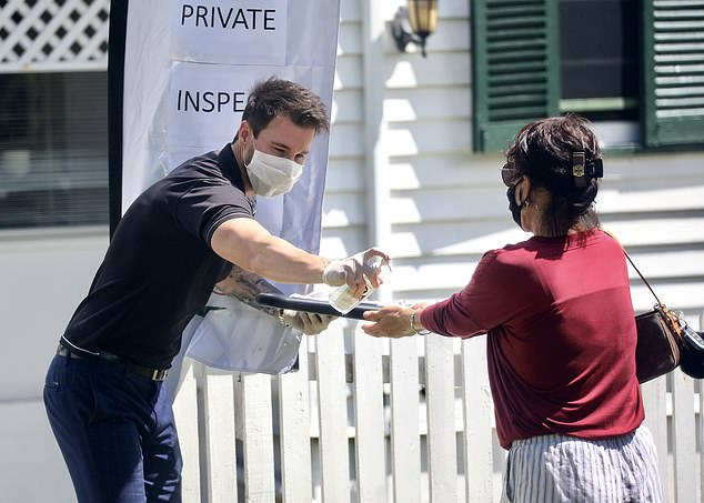 Taking all precautions: Michael kept a 1.5 metre distance and sprayed visitor's hands with sanitiser
