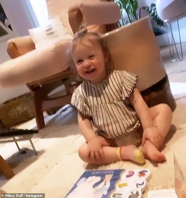 Children to think about: Duff flashed on her daughter Banks, 1, who was laughing in the background jovially, while playing with a baby book