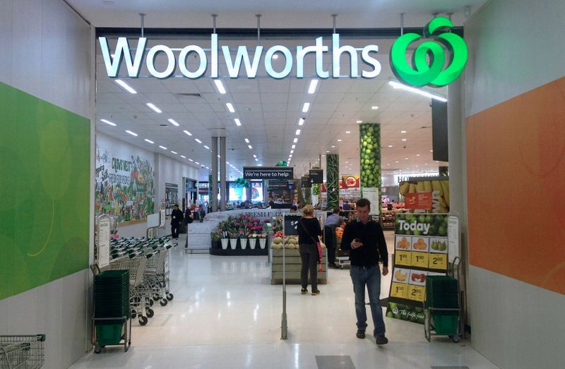 © Reuters. FILE PHOTO: A shopper walks out of a Woolworths store in Sydney, Australia