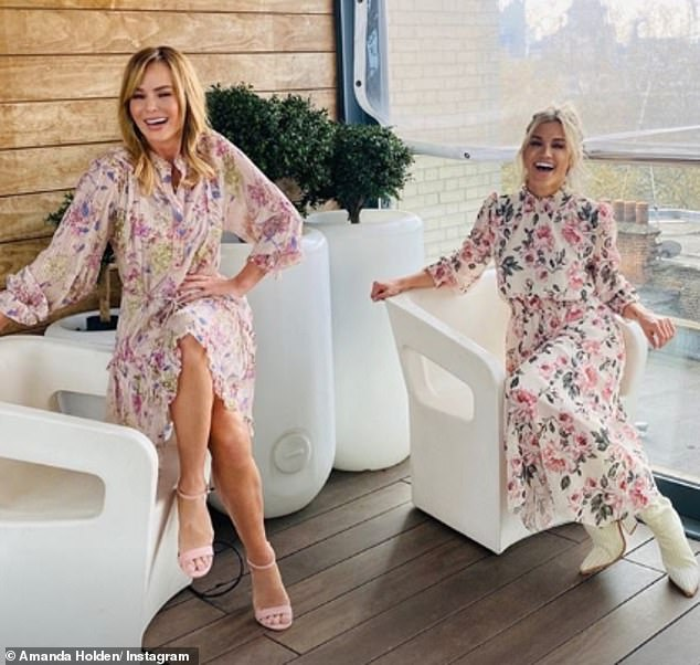 Matching: Amanda Holden and her radio co-host Ashley Roberts were 'twinning' in pink floral dresses on Wednesday at Heart FM as they continued to adhere to social distancing measures