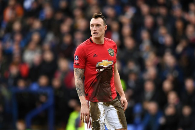 Phil Jones is covered in mud during a Manchester United game