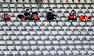 Medical staff sit in the stands.