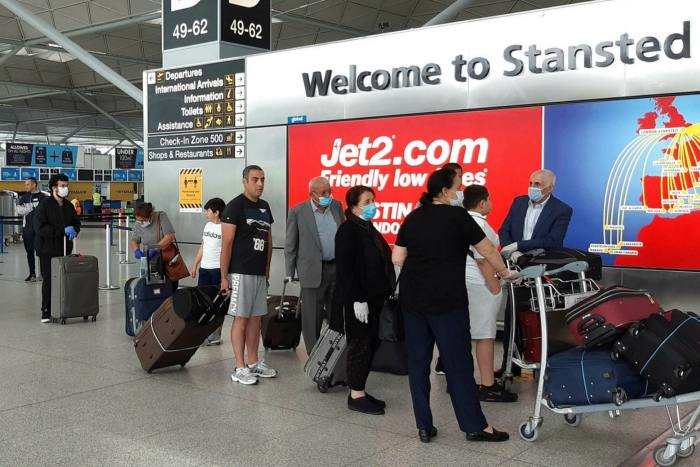 Passengers queue for a flight to Adana, Turkey at Stansted airport on June 3