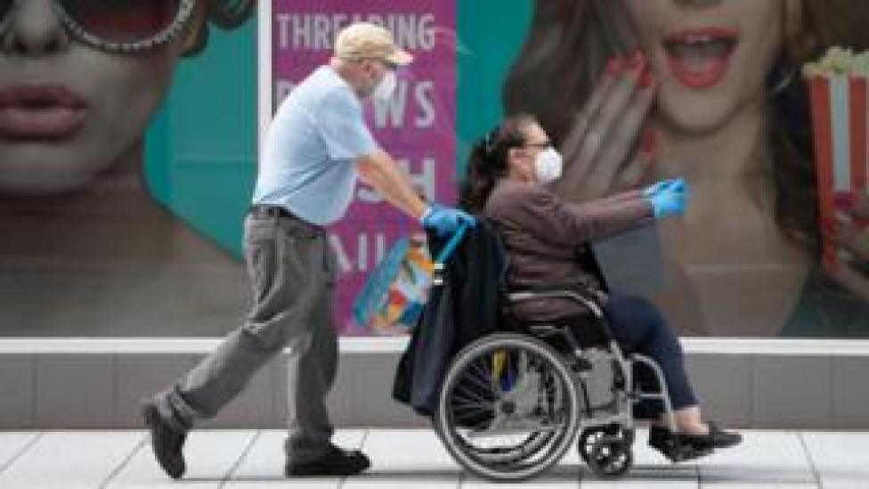 A woman sitting in a wheelchair wearing a mask and gloves, being pushed by a man wearing the same
