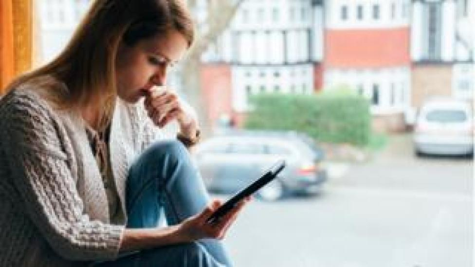 Woman sits in front of window on phone