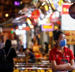 A beer brand promoter wearing a protective mask is seen as she waits for customers in front of a bar, at Ta Hien night street in Hanoi.
