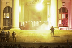 Protesters thrown flares at riot police on the steps of the parliament building in Belgrade.