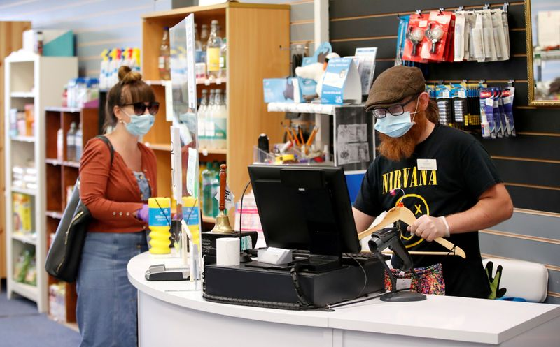 © Reuters. FILE PHOTO: An employee wearing a protective face mask serves a customers at Willen Hospice charity shop as it is re-opening for all customers after previously being open only for NHS employees, keyworkers and the elderly, following the coronavirus diseas