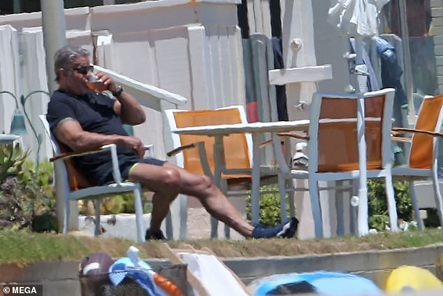 Kicking back:Sylvester Stallone enjoyed a break from his busy schedule as he enjoyed a cold drink at the beach in Malibu, California on Thursday