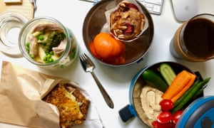 Jackie Middleton's office lunch pack, on a desk with pea, chicken and pesto pasta salad, pre-toasted cheddar cheese sandwich, crudités and hummus to dip, a mini muffin and seasonal fruit