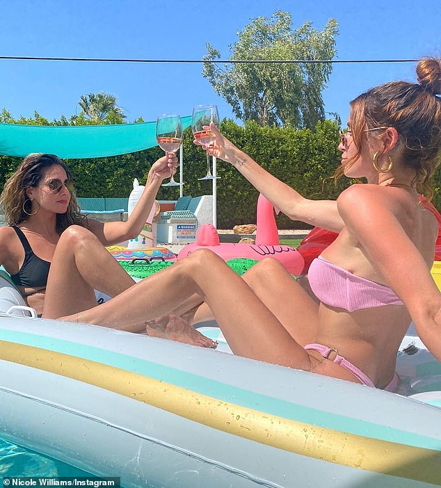 Cheers: She and her pal were also seen sipping rose wine in longstemmed glasses while on their floaties