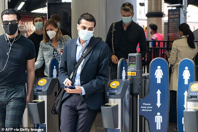 Commuters wearing face masks walk through the ticket barriers at Waterloo Station in London on June 15