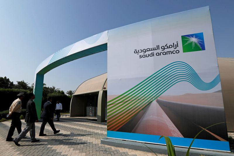 © Reuters. FILE PHOTO: Logo of Aramco is seen as security personnel walk before the start of a press conference by Aramco at the Plaza Conference Center in Dhahran