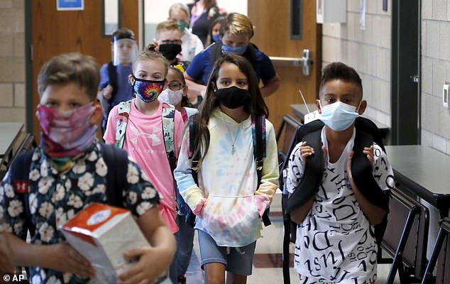 Researchers will track the percentages of children who become infected and household members who subsequently catch the virus. Pictured: Elementary school students walk to classes in masks to begin their school day in Godley, Texas, August 5