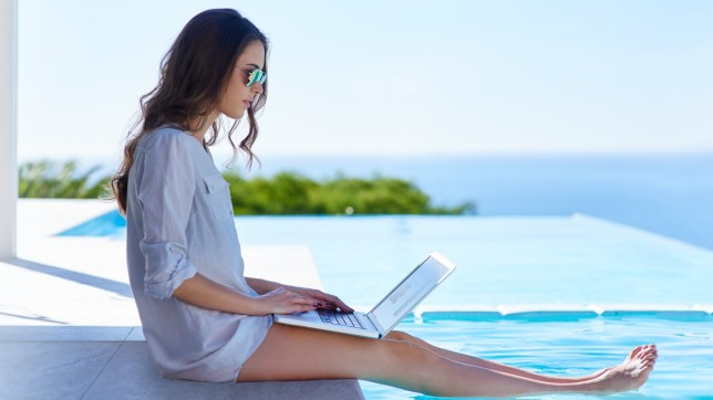 Shot of a young woman using her laptop by the poolside