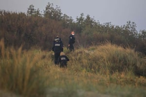 Police officers patrol the beach of Gravelines, near Dunkirk