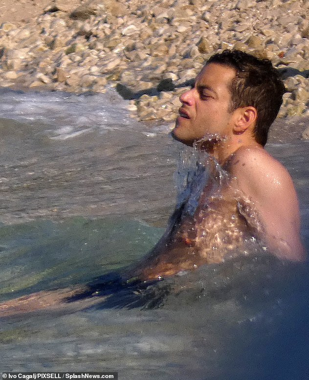 Care-free:Meanwhile Freddie Mercury actor Rami displayed his toned torso as he went shirtless in a pair of black swimming shorts for a dip in the crystal clear sea