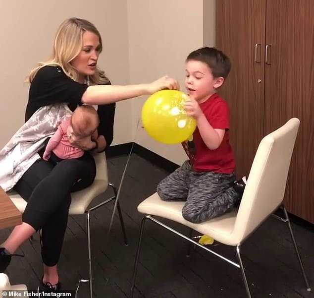 Doting mom: The new ACM entertainer of the year, plays with son's Isaiah, five, while holding other son Jacob, now 18 months, in a sweet snap to husband Mike's Instagram