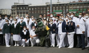 Medical workers who tend to Covid-19 patients and who received a medal from the government as recognition for their efforts pose for a photo with an Army mascot during the annual Independence Day military parade in Mexico City's main square of the capital, the Zócalo, Wednesday, 16 September 2020.