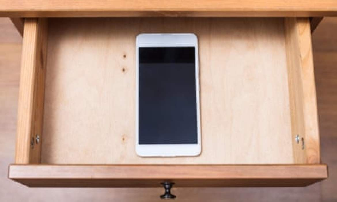 Above view of mobile phone in open drawer