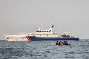 An offshore French patrol vessel confronts a migrants' dinghy