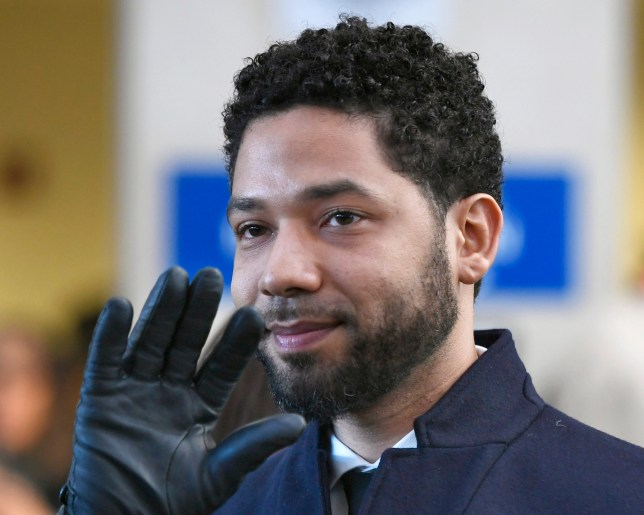FILE - In this March 26, 2019, file photo, actor Jussie Smollett smiles and waves to supporters before leaving Cook County Court after his charges were dropped in Chicago. Smollett's attorneys have filed a motion this week arguing that the actor should not have to pay the city of Chicago $130,000 for the police investigation into what he claimed was a racist and homophobic attack in January, because he had no way of knowing how much time and money the department would spend on the probe. (AP Photo/Paul Beaty, File)
