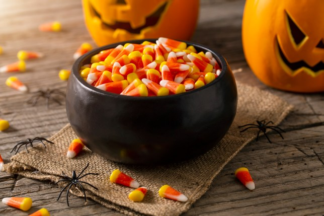 Bowl of Halloween candy corns with pumpkins and spider decorations.