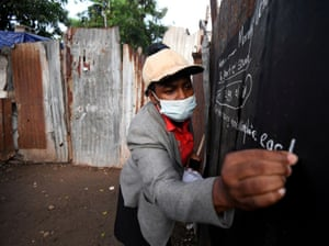 Educator Taneka Mckoy Phipps writes a lesson on a blackboard painted on a zinc fence, in a low-income neighbourhood in Kingston.